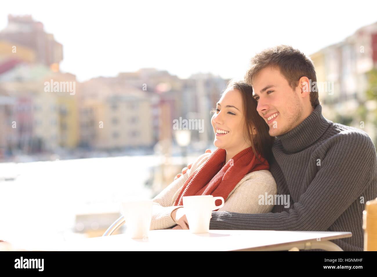 Paar, entspannend, sitzen in einer Hotelterrasse an Feiertagen mit einem Hafen im Hintergrund an einem sonnigen Stockbild