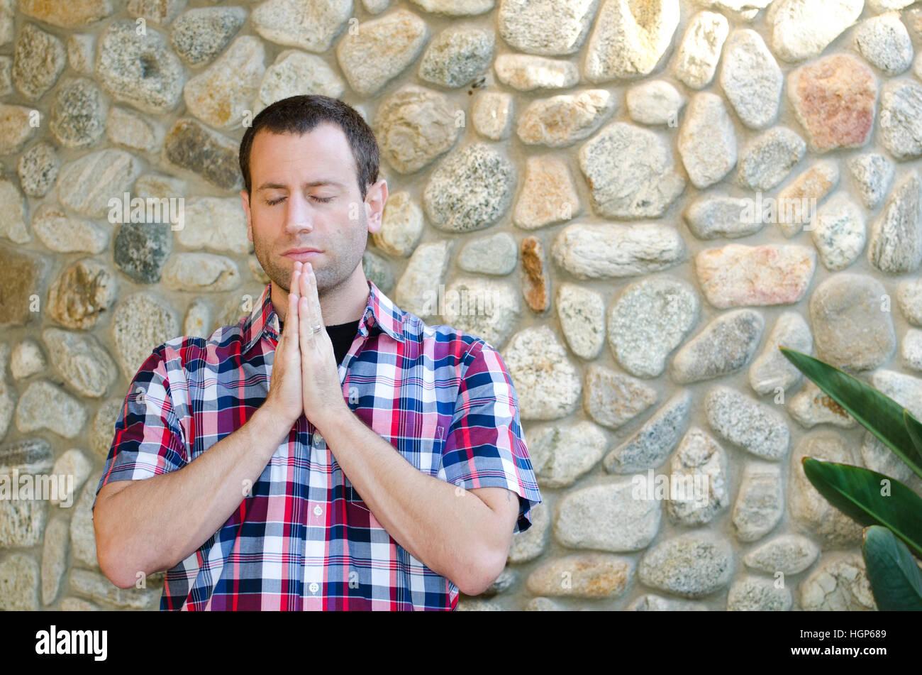 Mann, der betet außerhalb gegen eine Felswand. Stockfoto