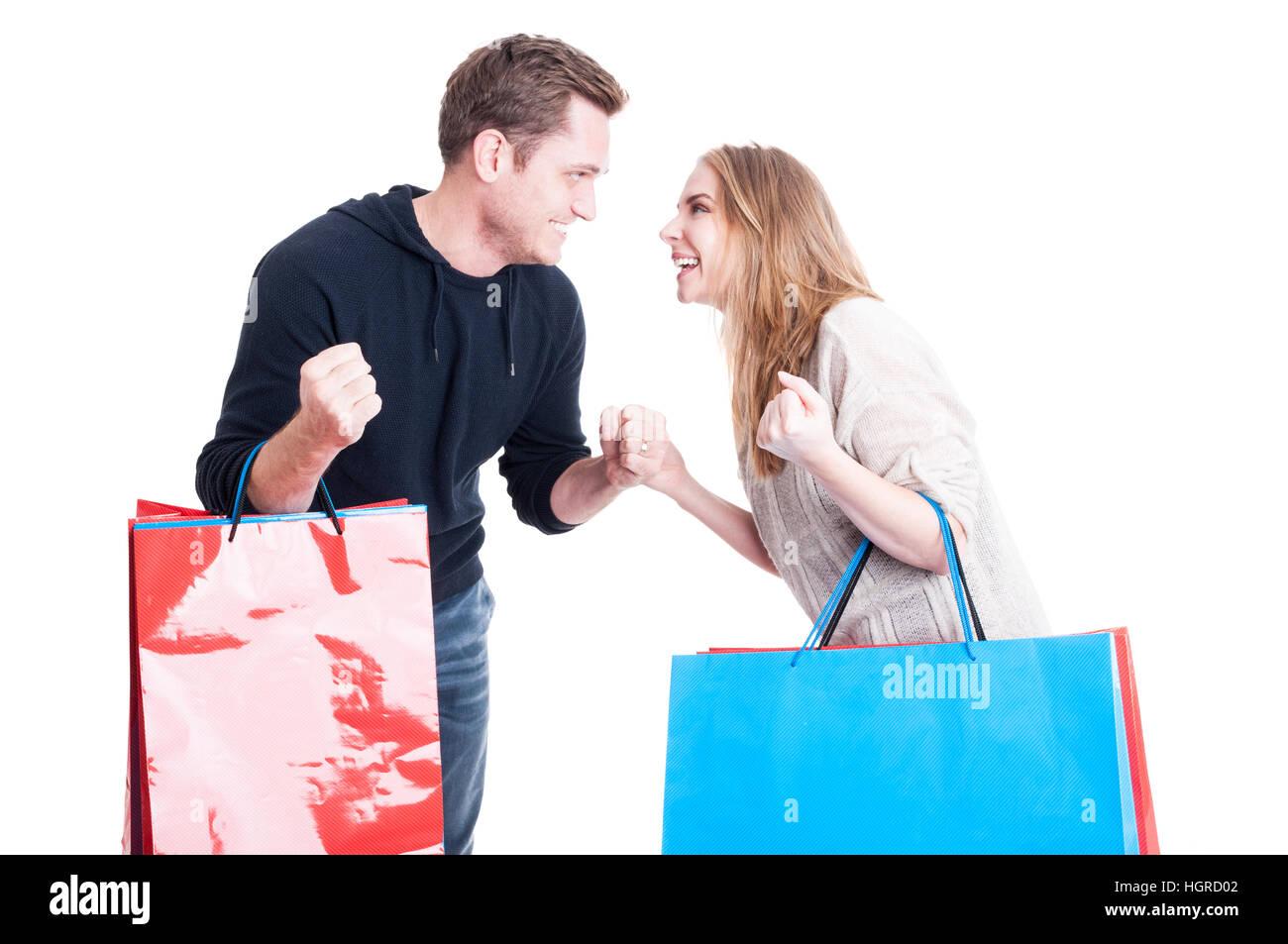 Paar halten Einkaufstaschen machen siegreichen Geste mit Fäusten, die isoliert voneinander betrachten und glücklich Stockbild