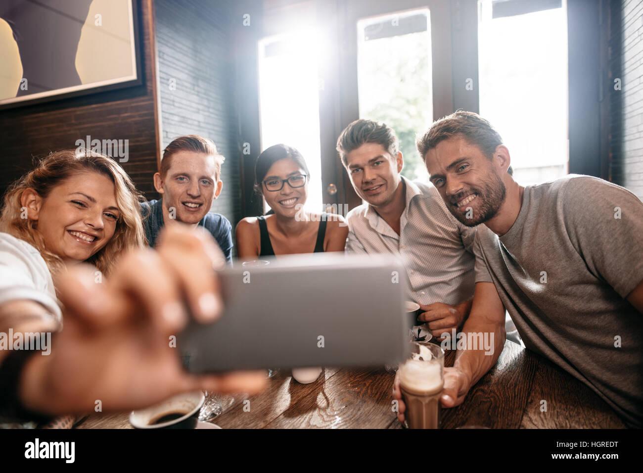 Heterogene Gruppe von Freunden nehmen Selfie auf Smartphone. Junge Männer und Frauen sitzen im Café-Tisch Stockbild