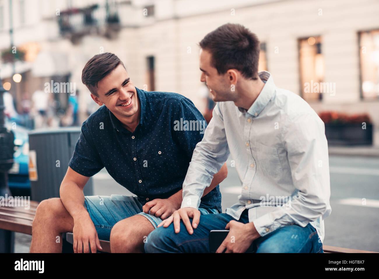 Freunde, die miteinander reden, auf einer Bank in der Stadt Stockbild