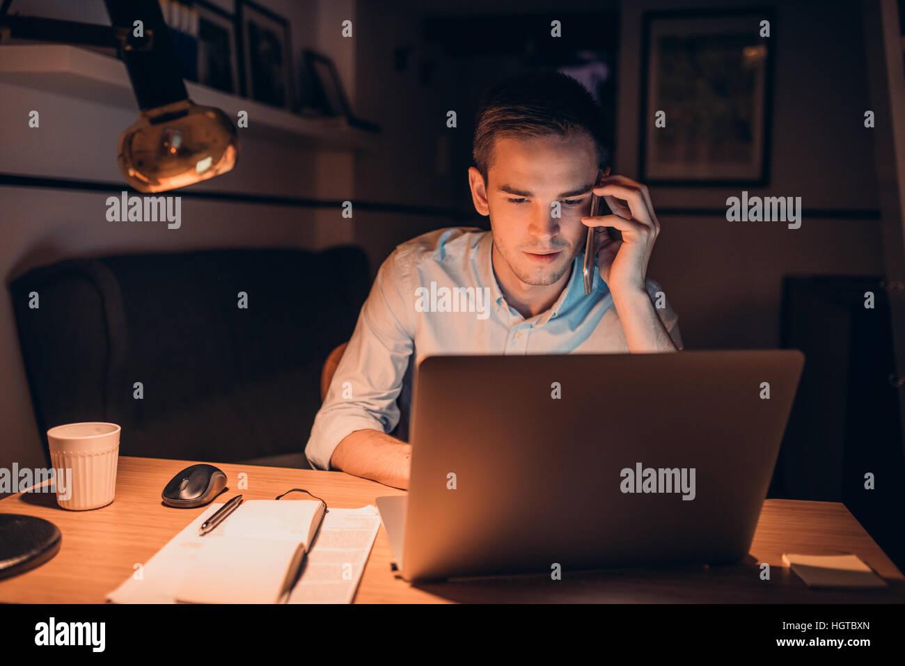 Junge Unternehmer bei der Arbeit in den späten Abend Stockbild