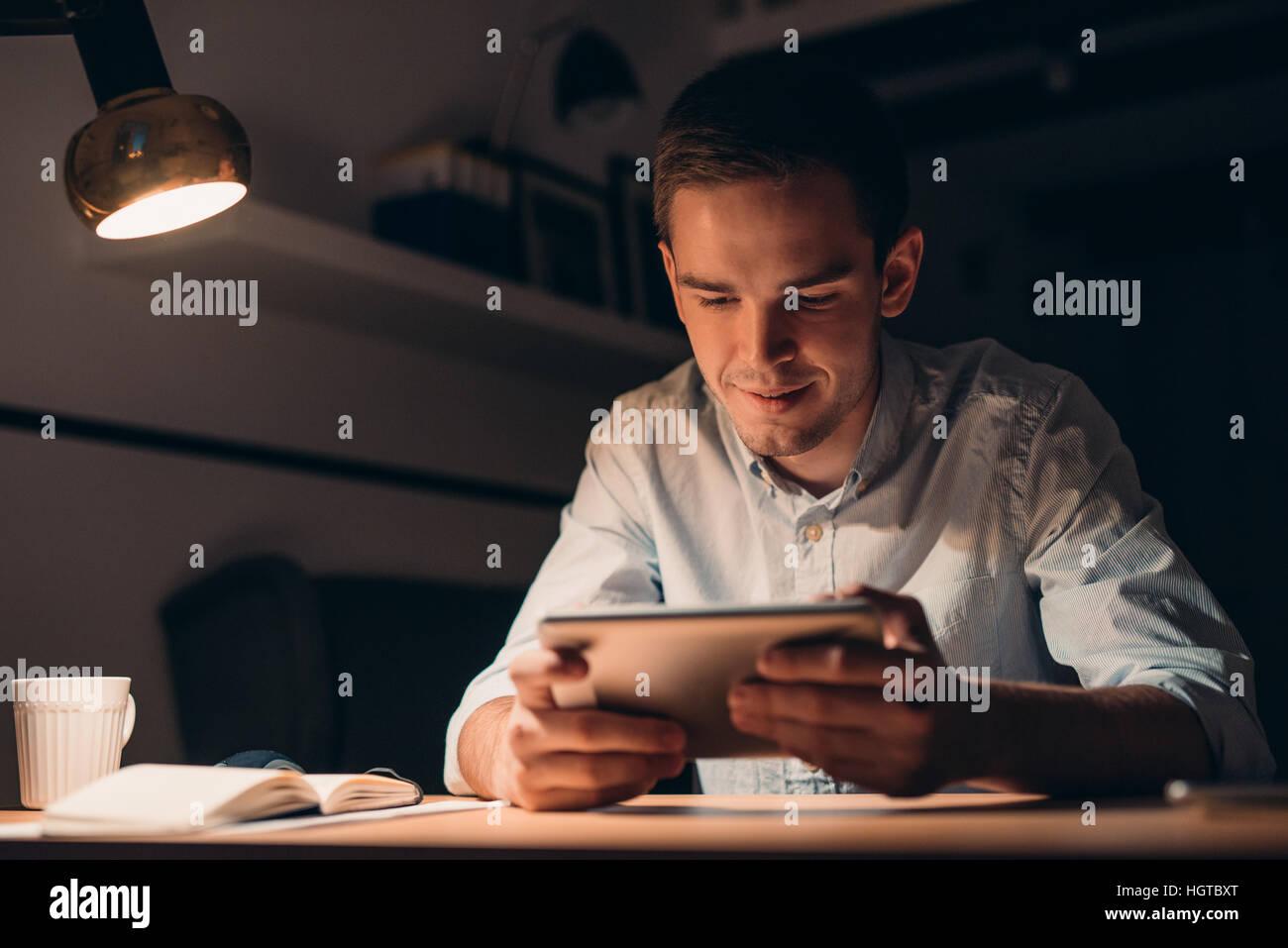 Junger Geschäftsmann mit einer Tablette spät in die Nacht arbeiten Stockbild