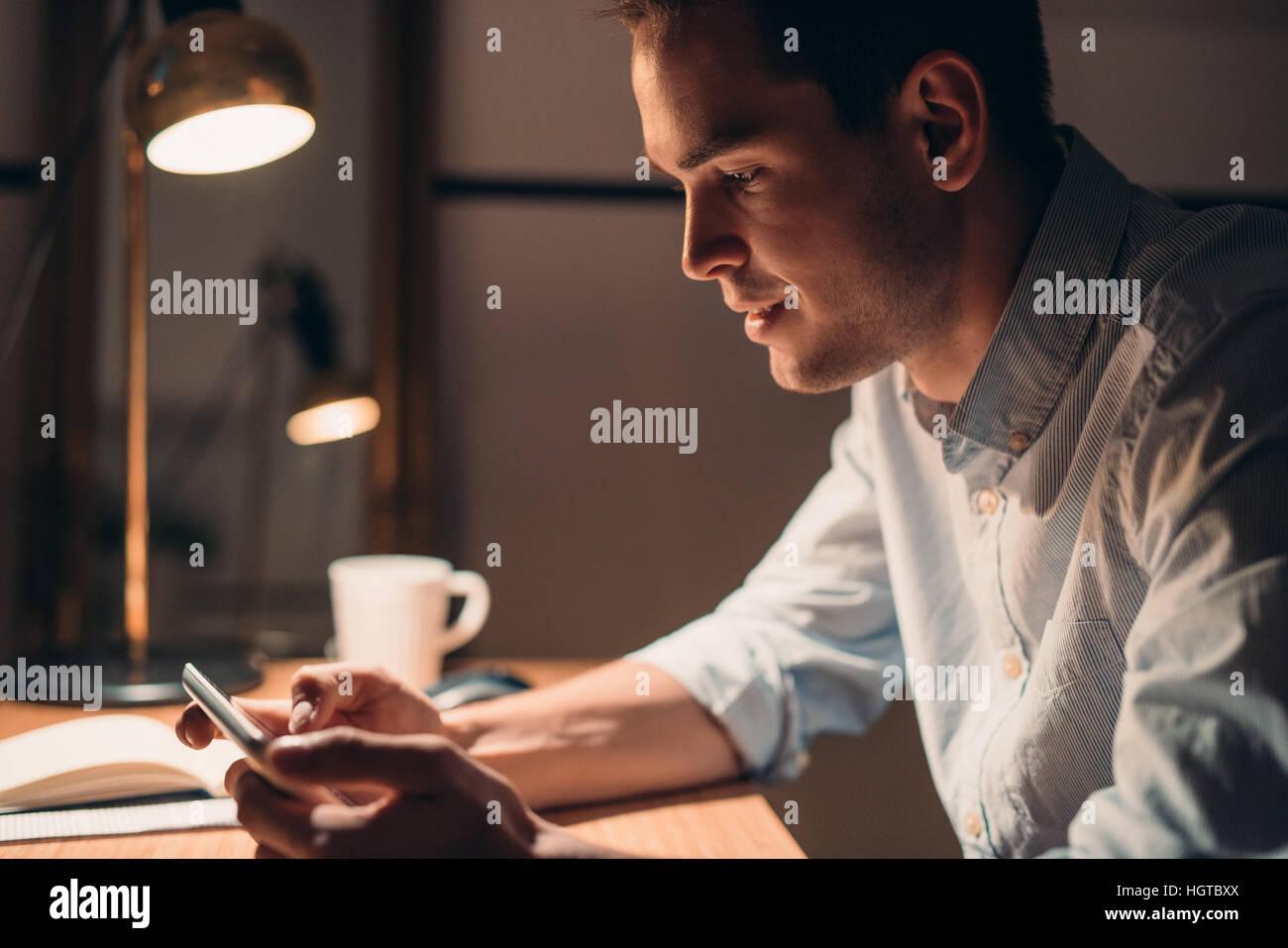 Junger Geschäftsmann auf einem digitalen Tablet spät in die Nacht arbeiten Stockbild