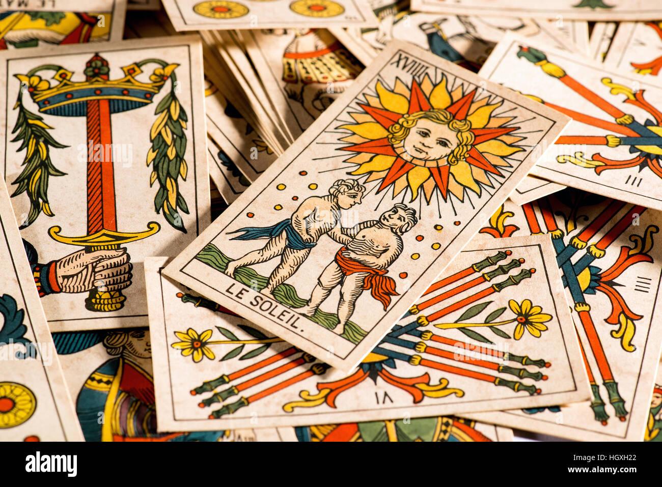 Ernte-Blick auf ungeordnete am Tisch mit einem mit der Sonne und Le Soleil Schild oben liegen viele Tarot-Karten Stockbild