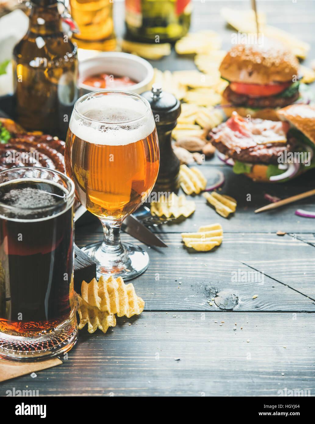Bier und Brotzeit Vielfalt auf dunklem Holz verbrannte Hintergrund Stockbild