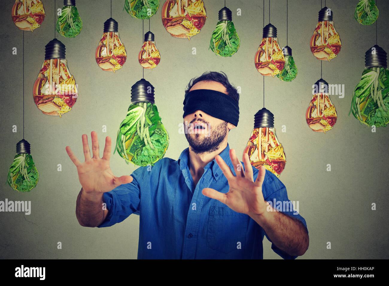 Mit verbundenen Augen Mann zu Fuß durch Glühlampen als Junk-Food grünes Gemüse grauen Hintergrund geprägt. Diät Stockfoto