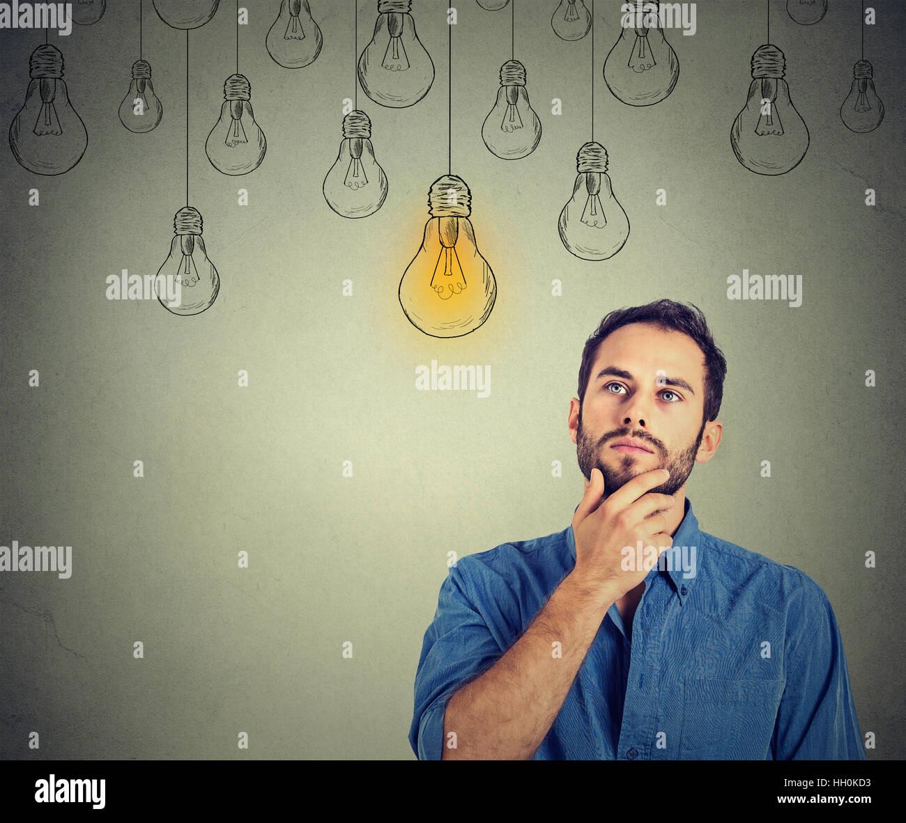 Porträt denken gut aussehender Mann blickte mit Idee Glühbirne über Kopf auf graue Wand Hintergrund Stockbild
