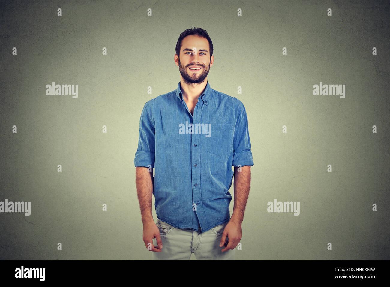 Porträt von ein hübscher junger Mann lächelnd vor grauen Wand Hintergrund isoliert Stockbild