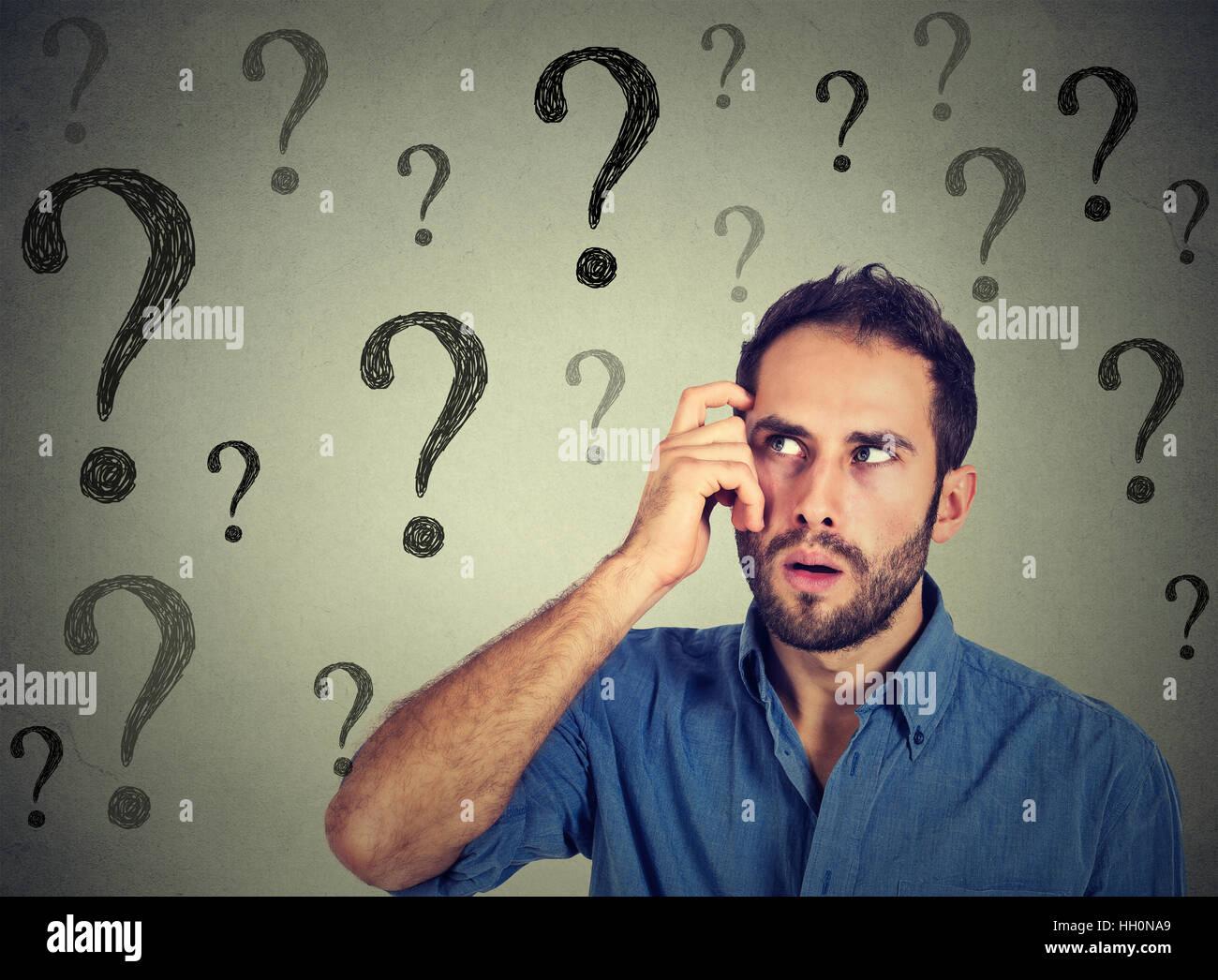 Nachdenklicher verwirrter gut aussehender Mann hat zu viele Fragen und keine Antwort Stockbild