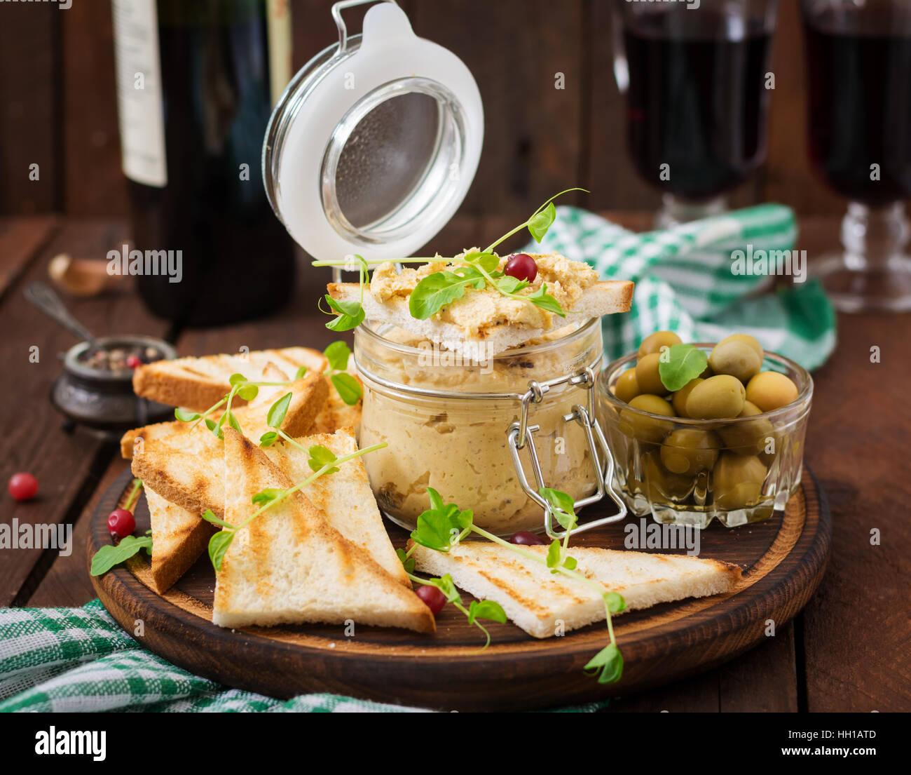 Pastete Huhn - Rillette, Toast, Oliven und Kräutern auf einem Holzbrett Stockbild