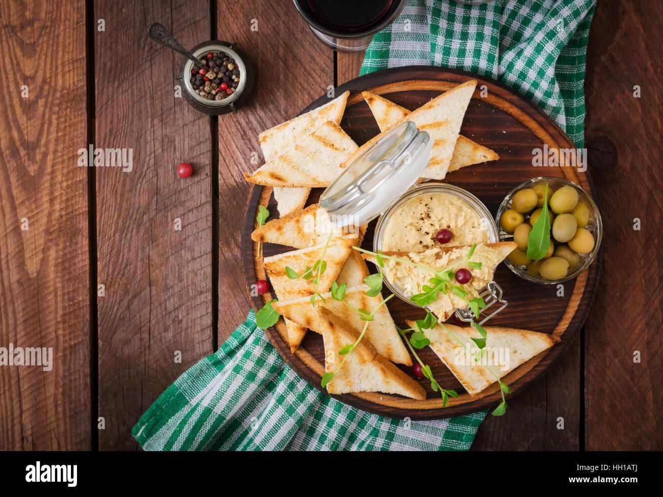 Pastete Huhn - Rillette, Toast, Oliven und Kräutern auf einem Holzbrett. Flach zu legen. Ansicht von oben Stockbild