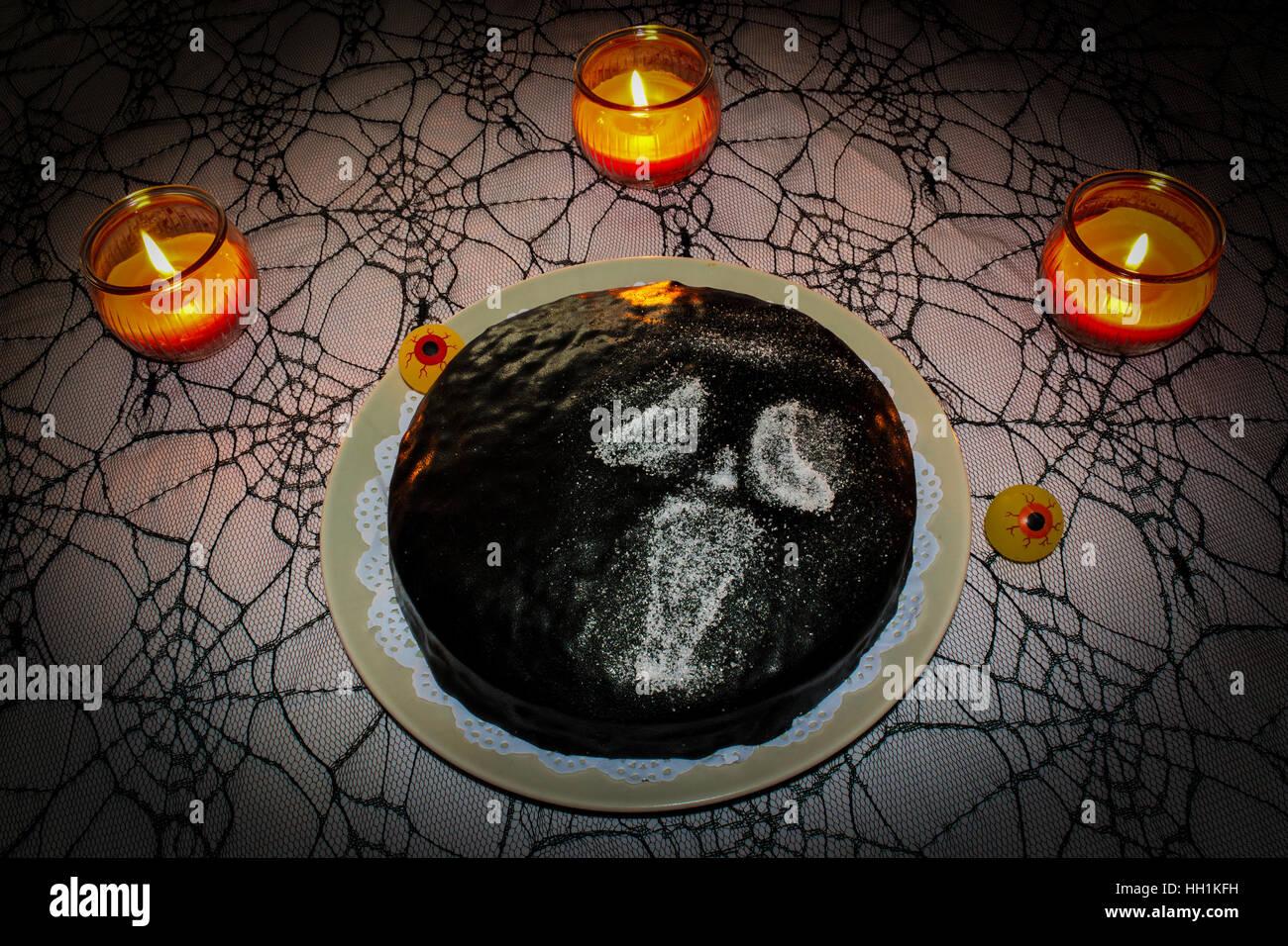 Halloween Kuchen auf Spinne Tischdecken und Kerzen Stockbild
