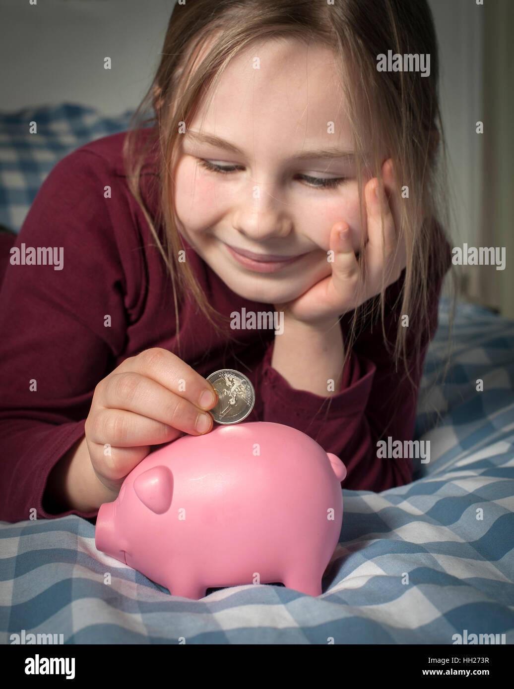 Junges Mädchen ihre Euro-Geld in ein Sparschwein zu sparen. Stockbild