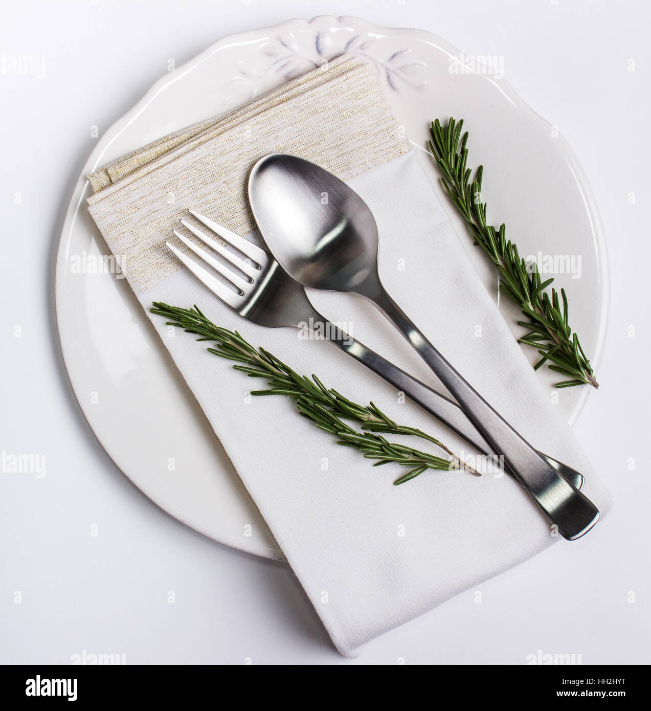 Schöne Teller, Löffel und Gabel auf einer Serviette mit Rosmarin zur ...