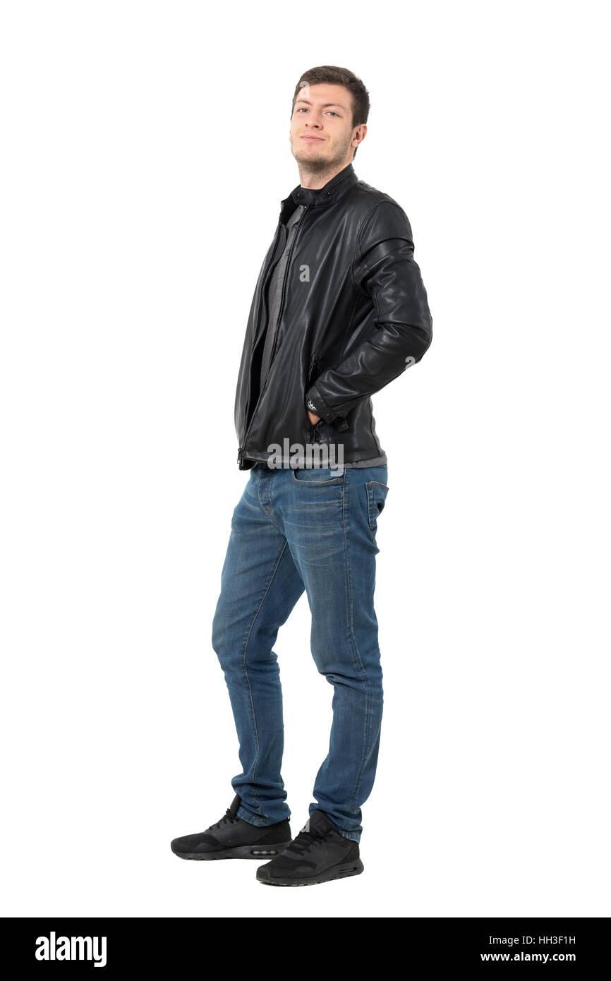 Seitenansicht des Jünglings lässig in Jeans und Lederjacke in die Kamera Grinsen. Ganzkörper-Länge-Porträt isoliert Stockfoto
