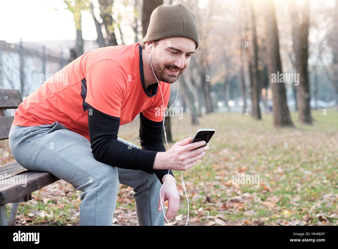Junger Mann im Stadtpark trainieren und mit seinem Handy Stockbild