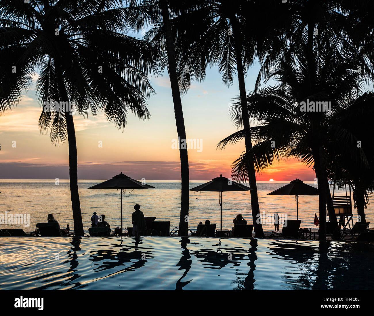 Atemberaubenden Sonnenuntergang mit Palmen, die Reflexion über das Schwimmbad in Koh Chang, einer beliebten Stockbild