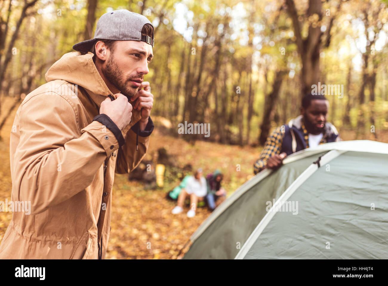 Junge Männer pitching Zelt im herbstlichen Wald mit unscharfen Mädchen sitzen auf Hintergrund Stockbild