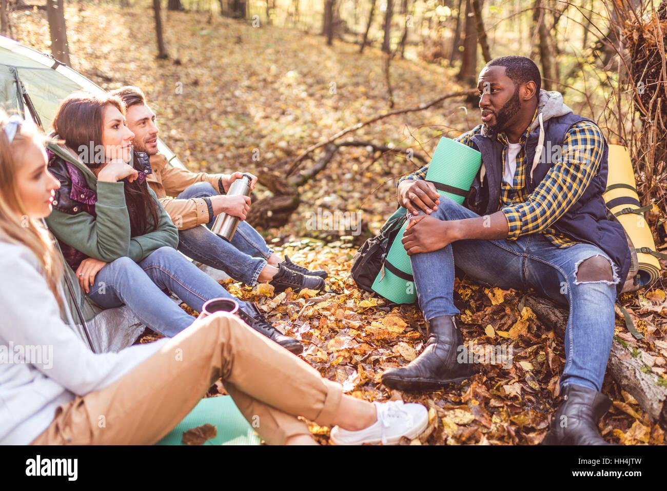 Junge Freunde Reisende sitzen und reden in der Nähe von Zelt im herbstlichen Wald Stockbild