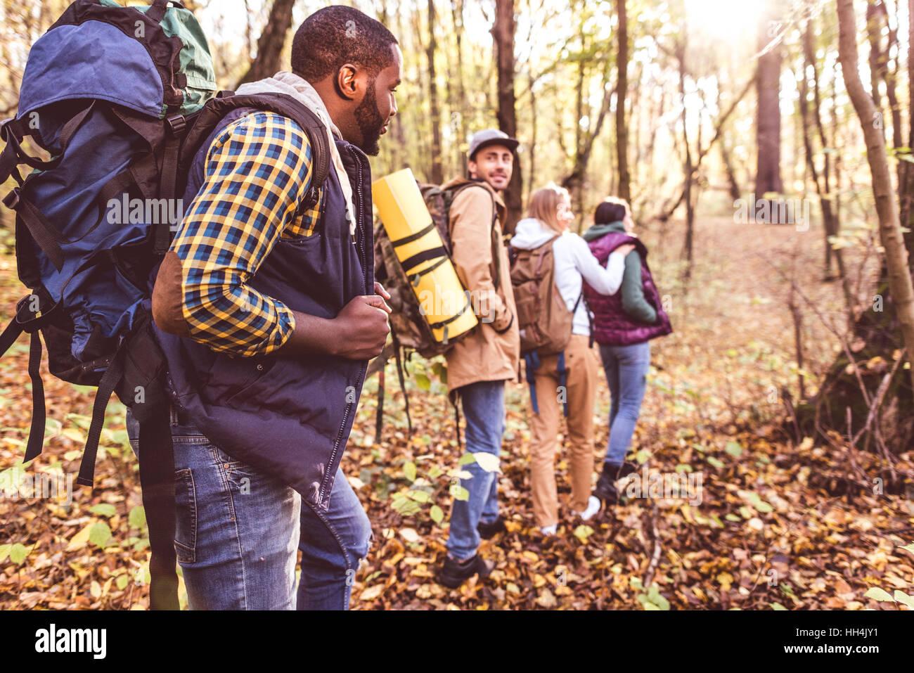 Vier junge Rucksacktouristen Wandern hintereinander im herbstlichen Wald bei Sonnenuntergang Stockbild