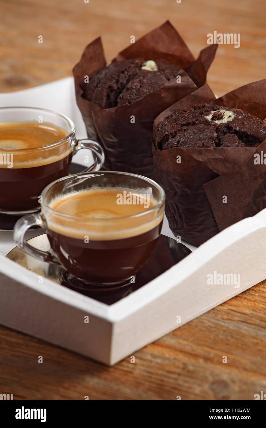 Foto von zwei feuchten Schokoladen-Muffins und zwei Tassen Espresso oder Kaffee ruht auf einer weißen Serviertablett. Stockbild