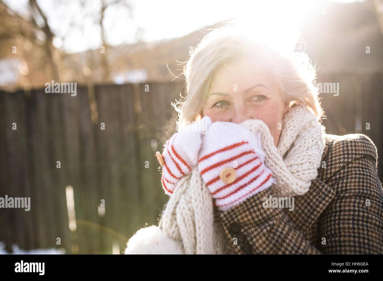 Schöne ältere Frau auf einem Spaziergang gegen Holzzaun. Stockbild
