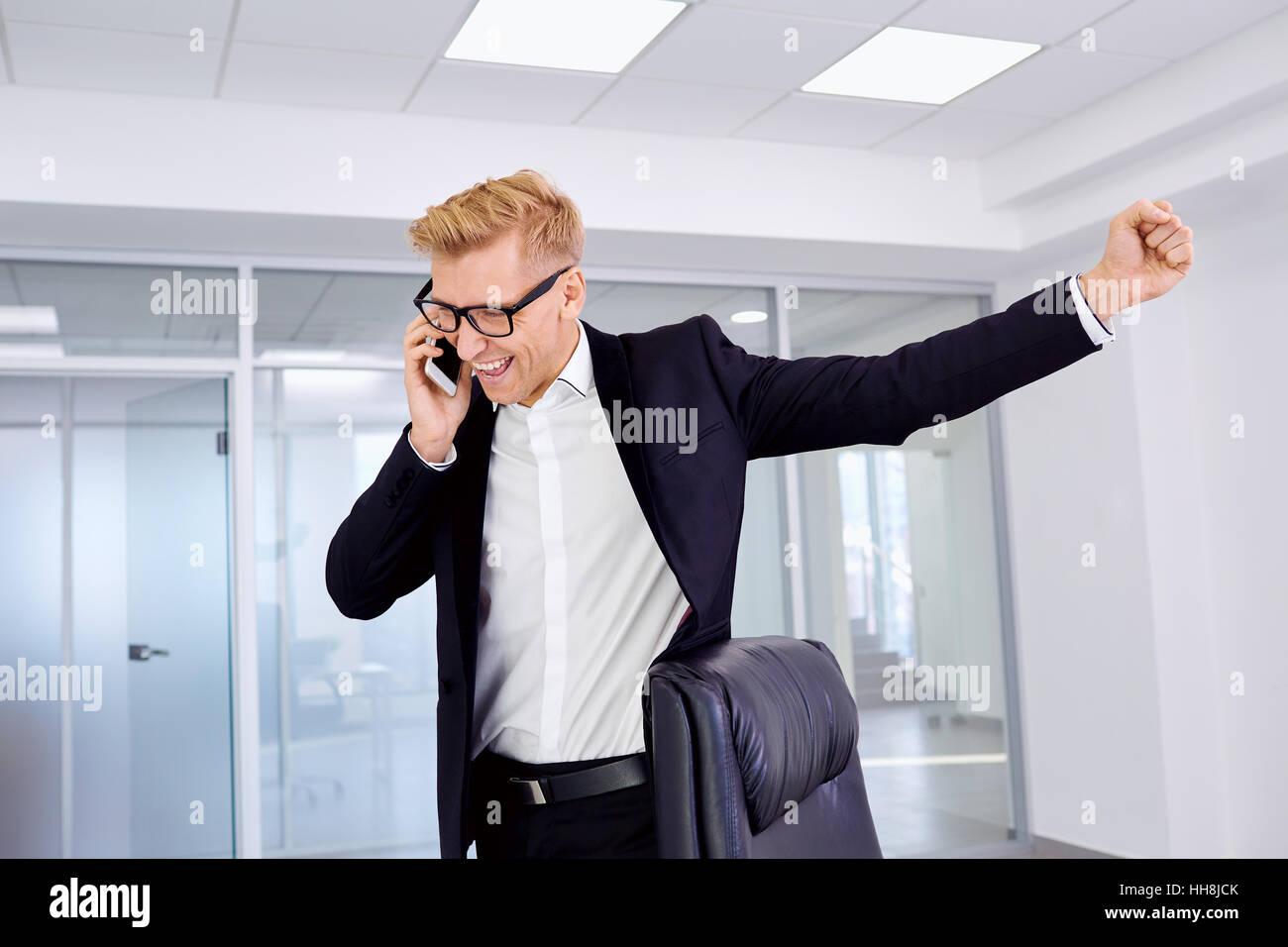 Das Konzept der Erfolg, Sieg, Business. Geschäftsmann Blondine mit Brille hob die Faust, am Telefon Lächeln, Stockbild