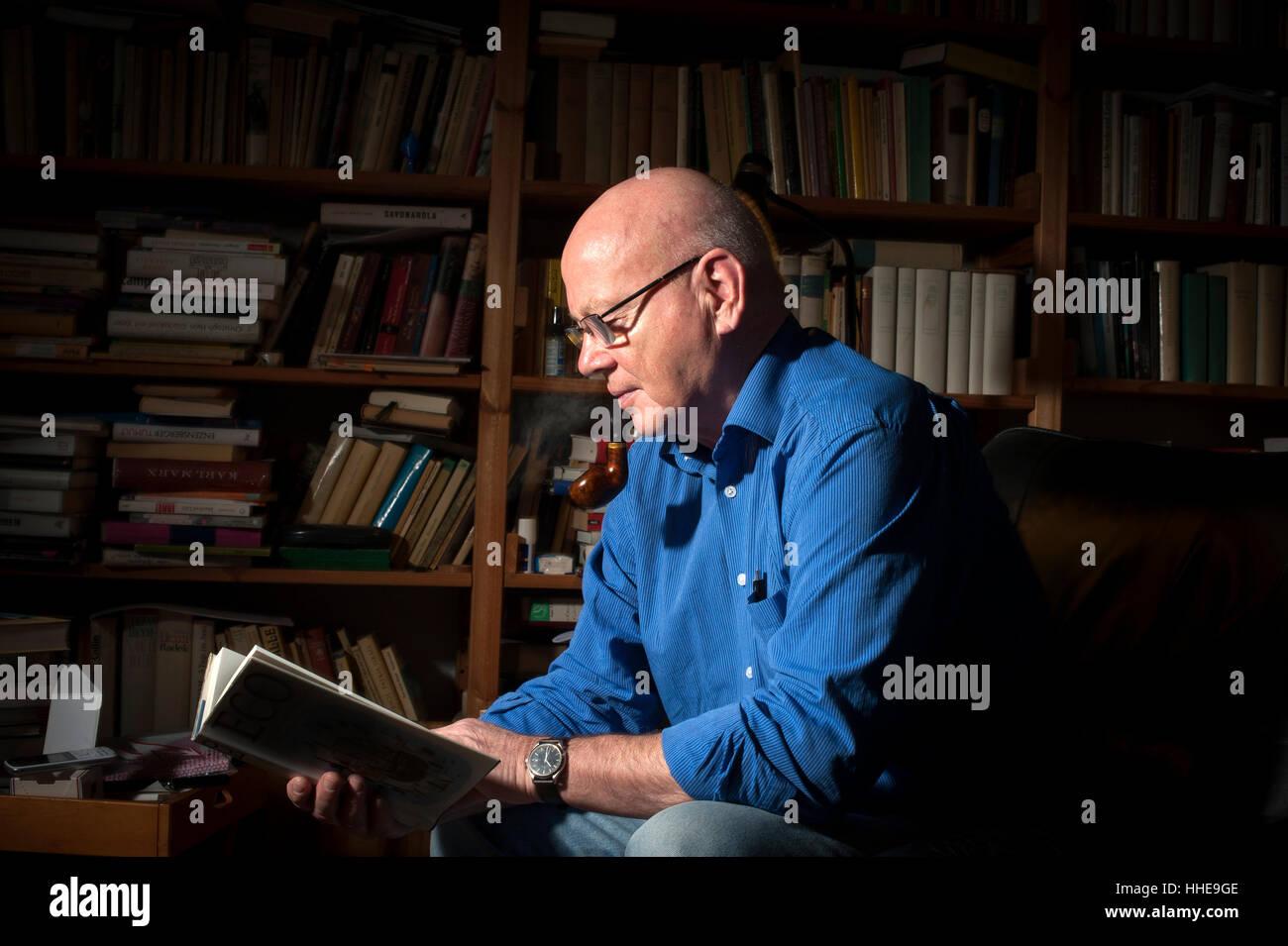 Ein Rentner in seinem Arbeitszimmer zu Hause lesen. Stockbild