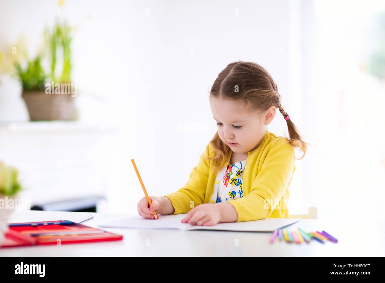 Niedliche kleine Mädchen Hausaufgaben machen, ein Buch zu lesen ...