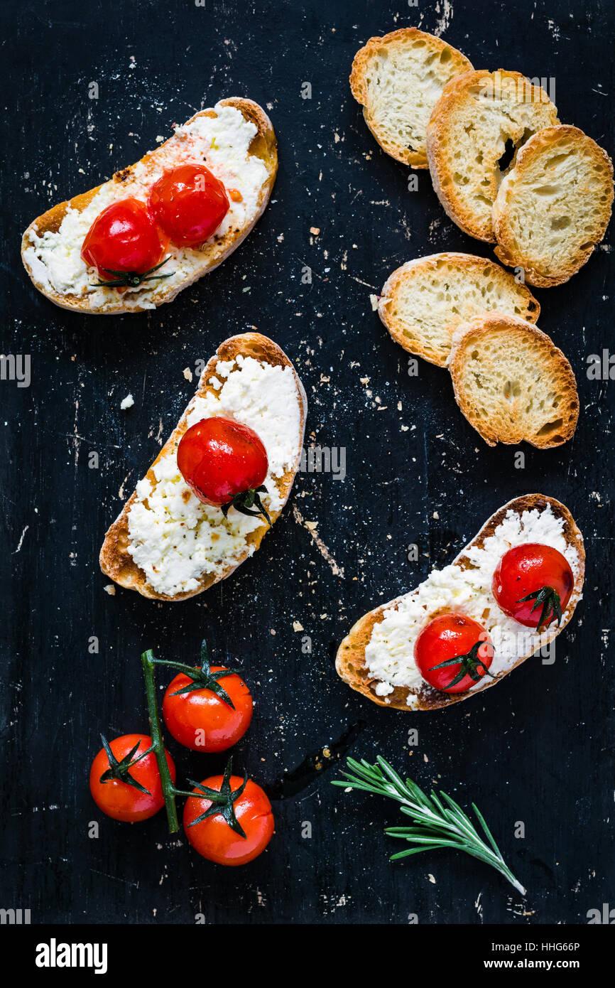 Toast-Crostini mit frischen weißen Käse Ricotta, geröstete Cherry Tomaten und Knoblauch Olivenöl Stockbild