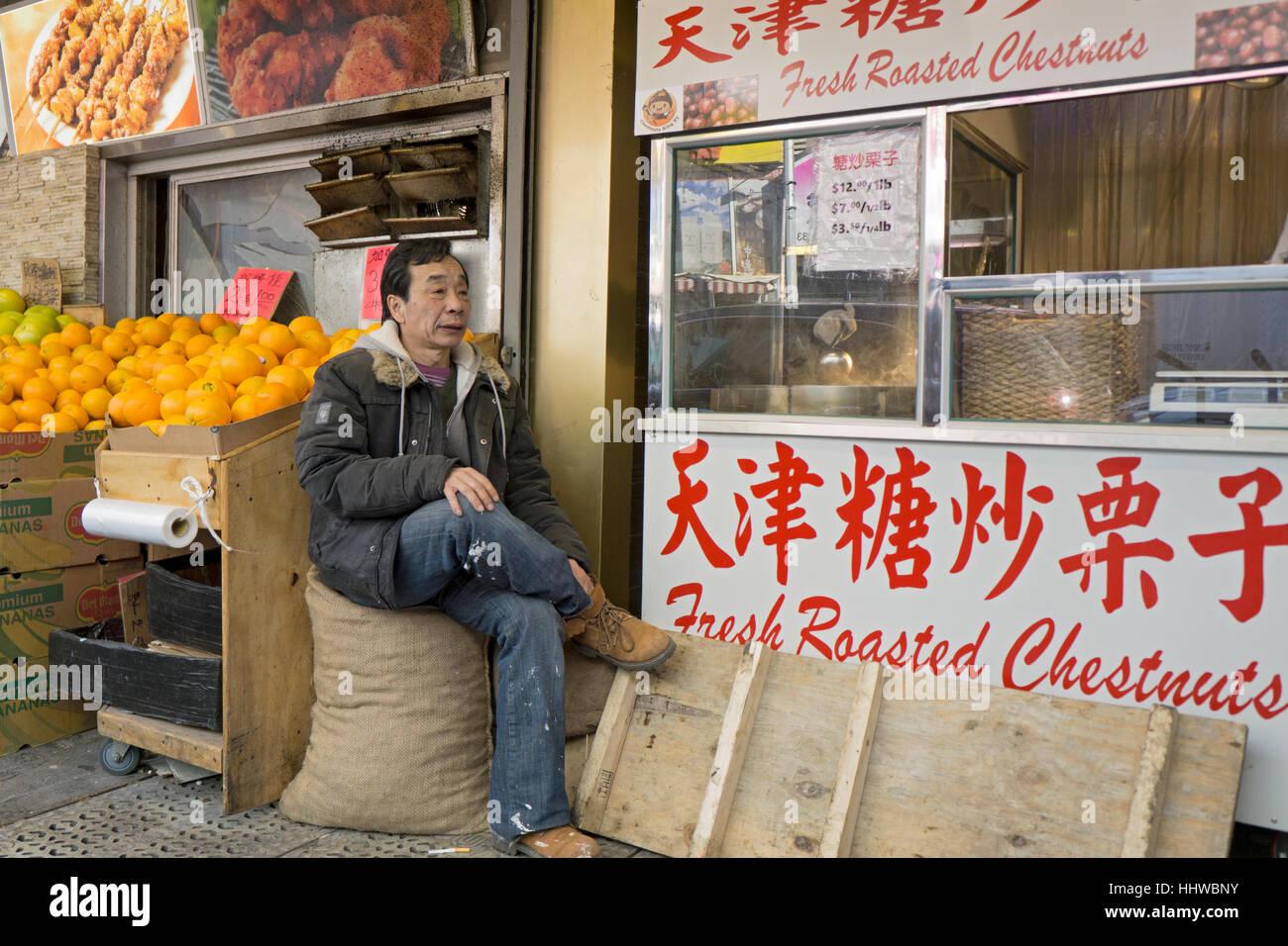 Ein chinesische amerikanische Arbeiter nimmt eine Arbeitspause in einer Seitenstraße in Chinatown, Downtown Stockbild