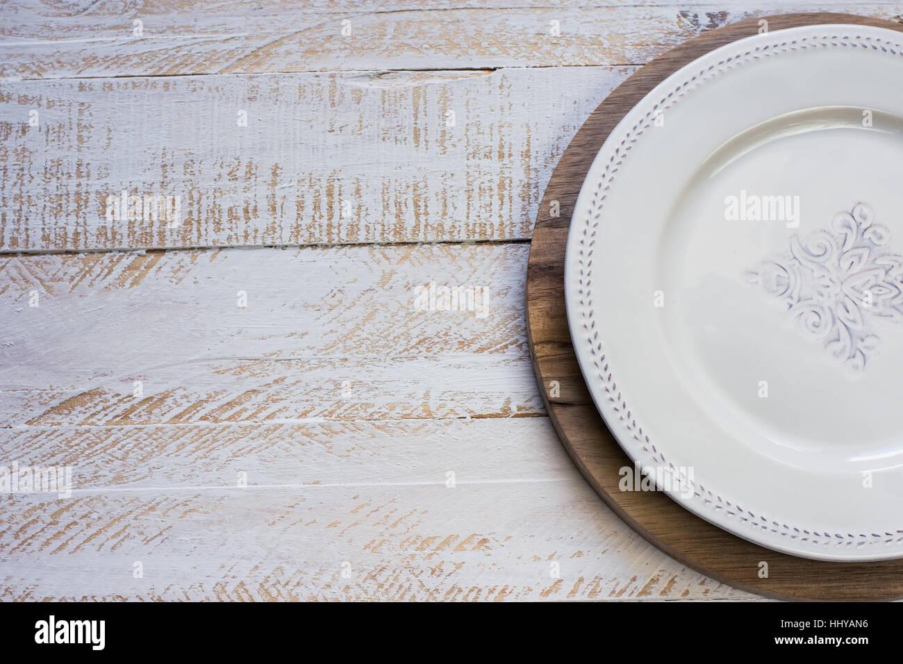 Weiße vintage leeren teller auf runden schneidebrett weißen brett