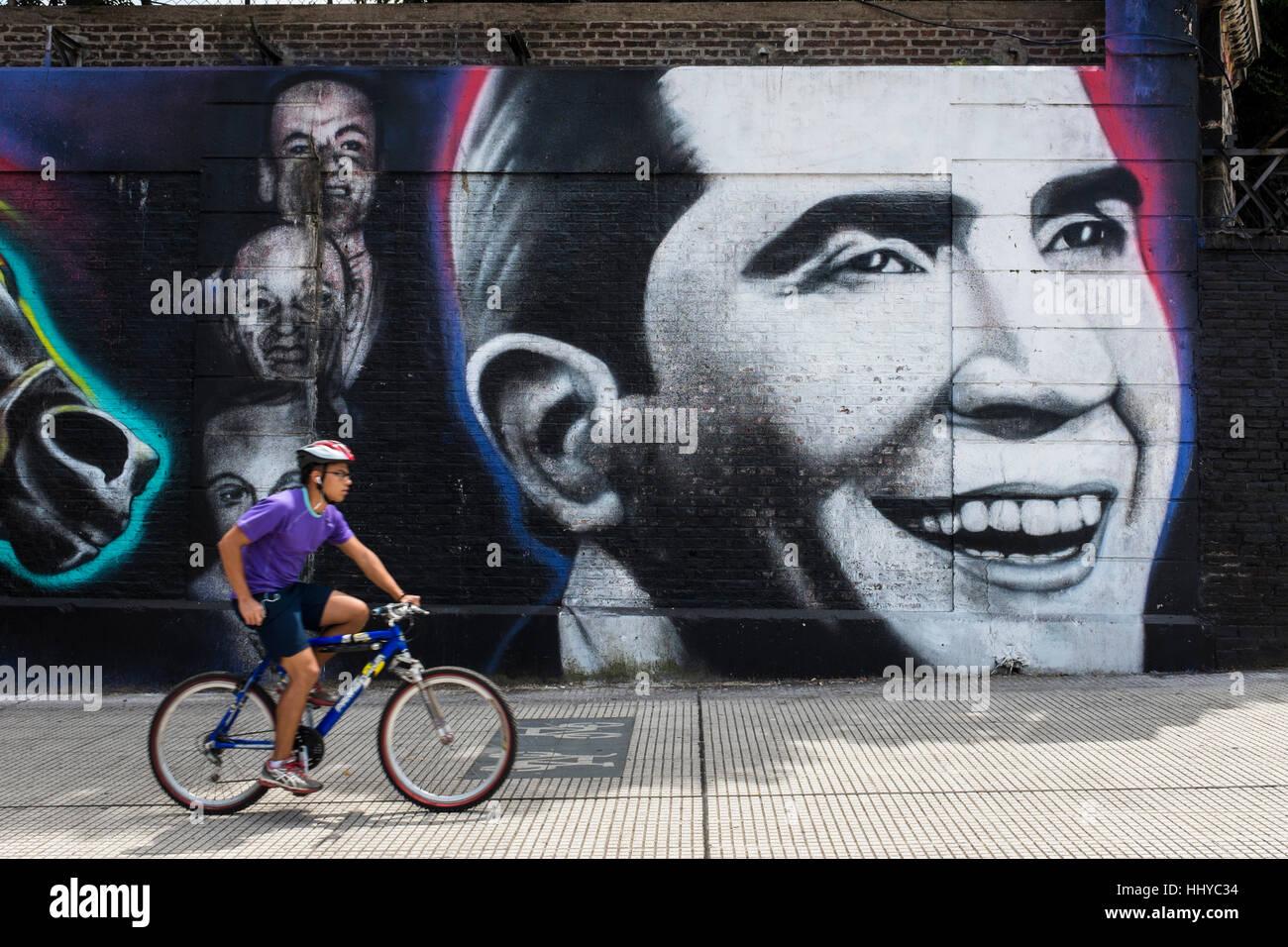Radfahrer geht ein Wandbild von Tango-Sänger Carlos Gardel in Stadt Buenos Aires, Argentinien. Stockbild