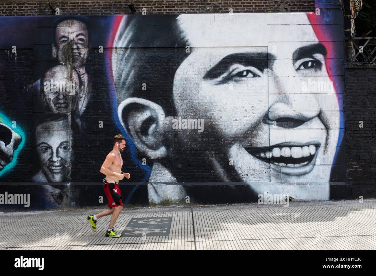 Jogger führt vorbei an einer Wandmalerei von Tango-Sänger Carlos Gardel in Buenos Aires Stadt Stockfoto