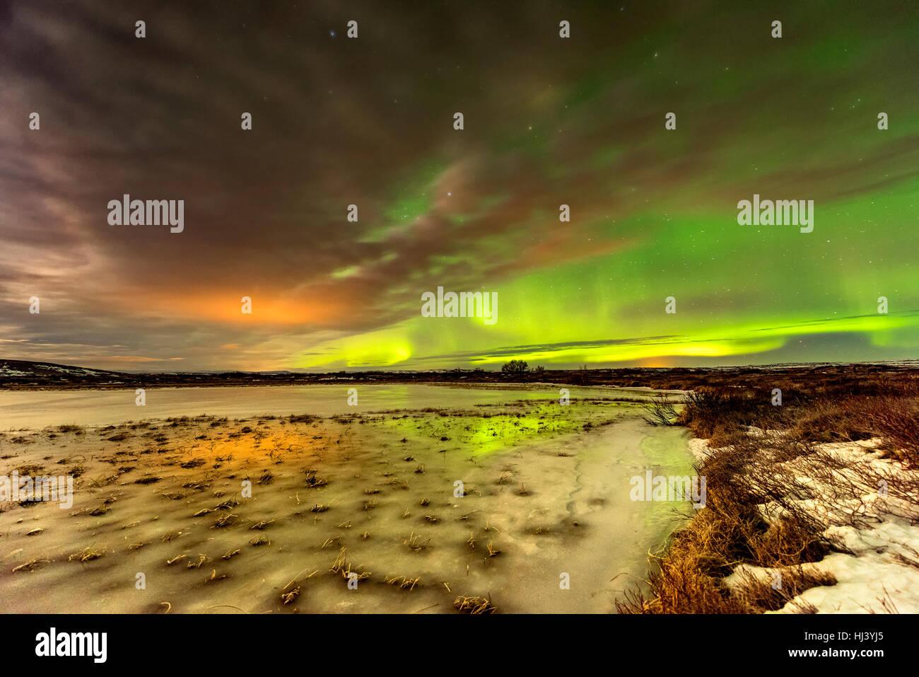 Aurora Borealis leuchtet über einen gefrorenen See, umgeben von niedrigen Wolken und Sterne Stockbild