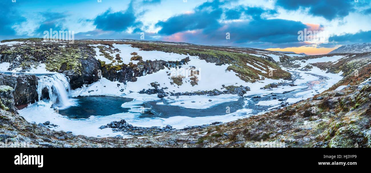 Ein kalten verschneiter Wasserfall im Hochland von Island umrahmt von Pastell Himmel und zerklüftete Gelände Stockbild
