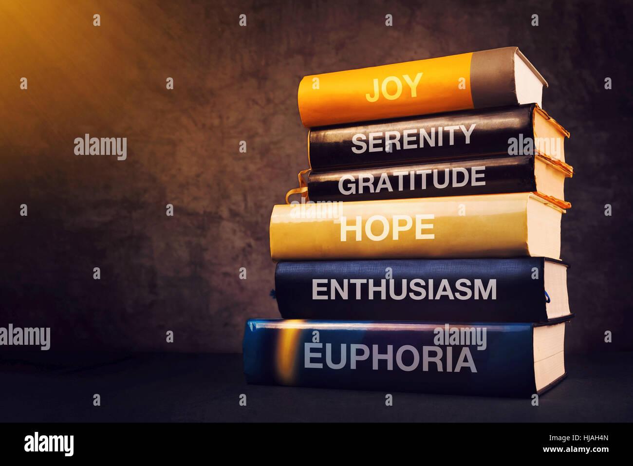Positive Emotionen und Gefühle-Konzept mit Buchtitel auf Bibliothek Regal - Freude, Gelassenheit, Dankbarkeit, Stockbild