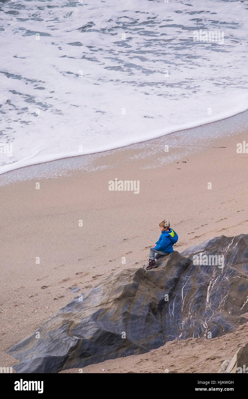 Ein kleiner Junge sitzt alleine auf einem Felsen am Strand von Little Fistral, Newquay, Cornwall, England. Stockbild
