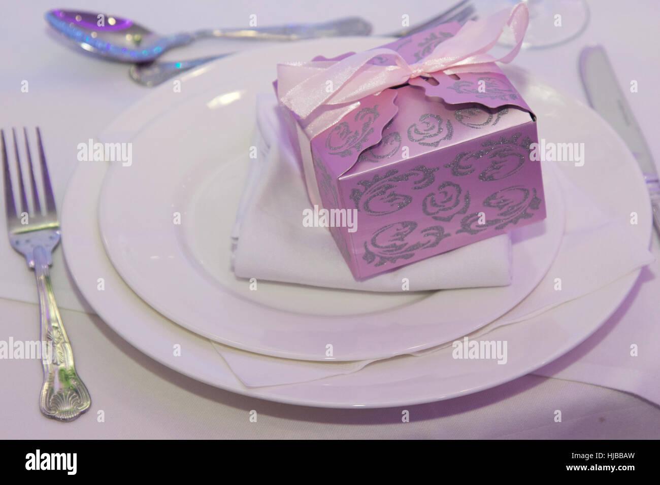 Geschenkbox mit Schleife auf weißen Tellern mit Messer, Gabel und ...