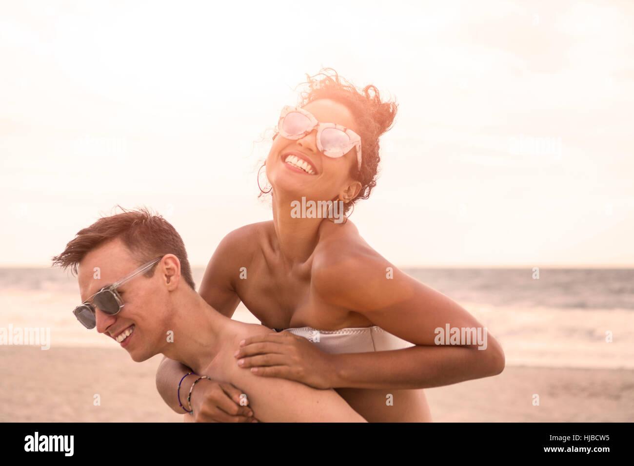 Junger Mann mit Huckepack Freundin auf Rockaway Beach, New York State, USA Stockbild