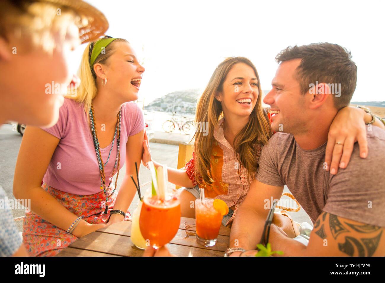 Zwei Erwachsene Paare lachen bei einem Cocktail im Waterfront Restaurant, Mallorca, Spanien Stockbild