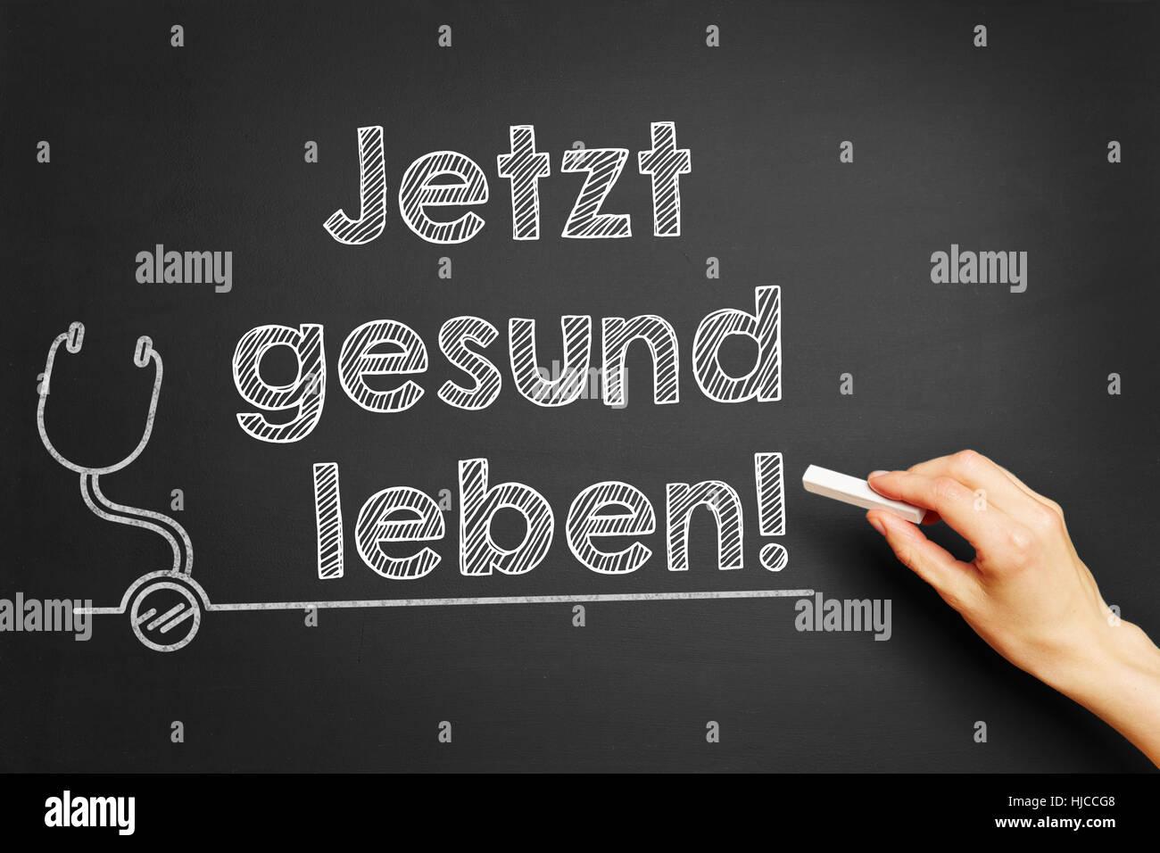 """Hand, schreibt in Deutsch """"Jetzt Gesund Leben!"""" (Leben Sie gesund jetzt!) auf Tafel Stockbild"""