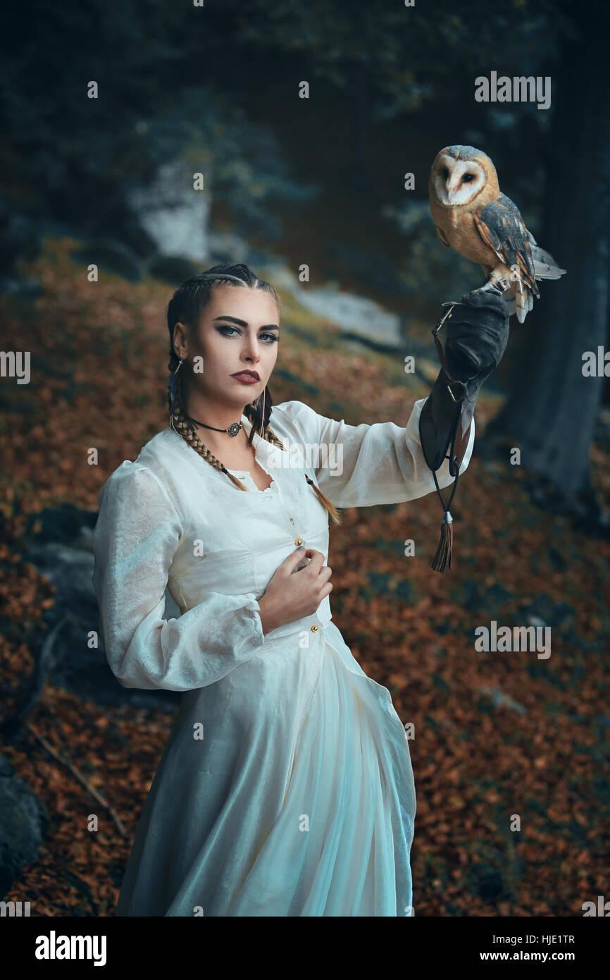 Elegant gekleidete Frau mit Schleiereule. Fantasie und Falknerei Stockbild