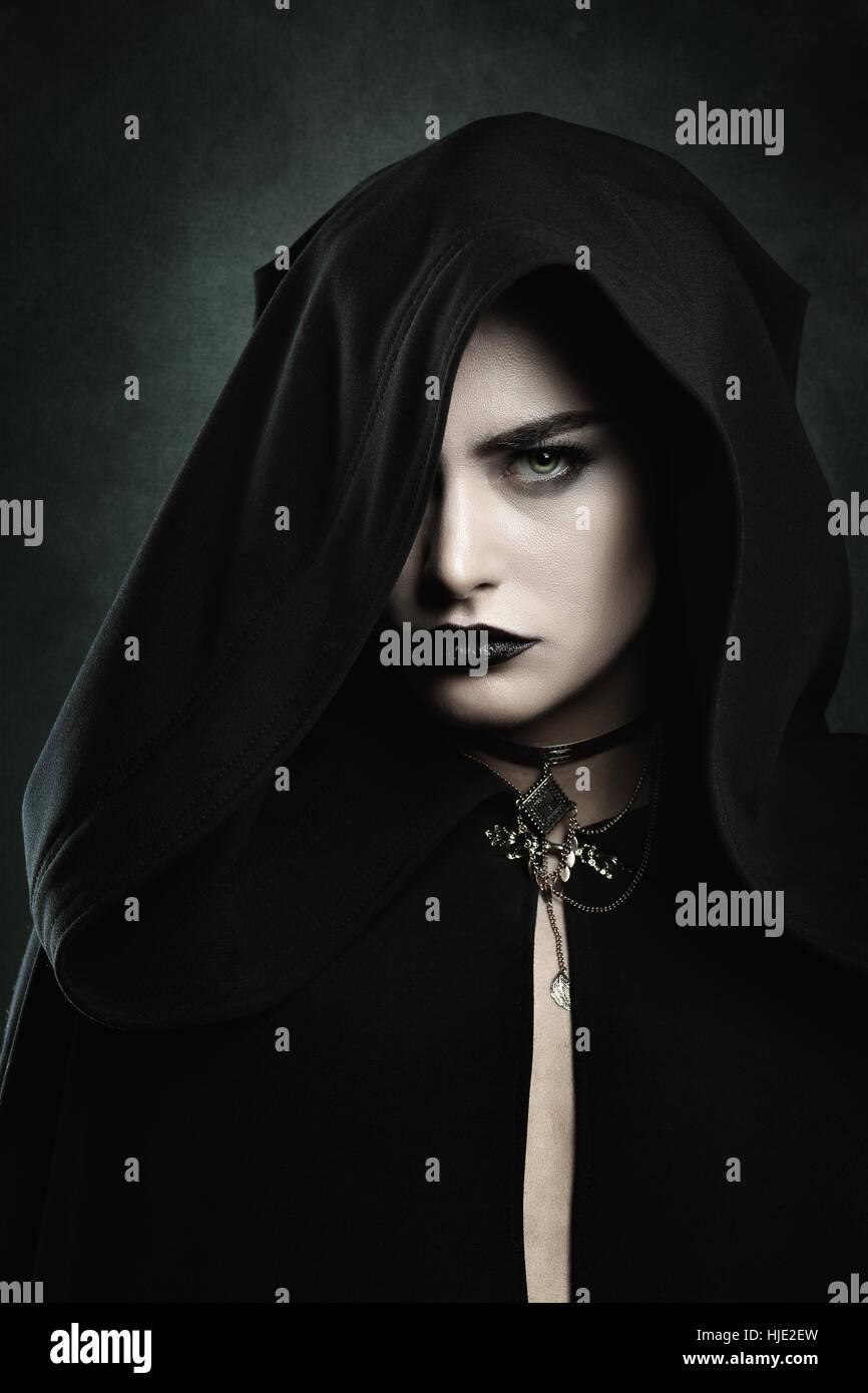 Dunkle Porträt einer schönen Vampir-Frau mit schwarzer Kapuze. Halloween und Horror-Konzept Stockbild