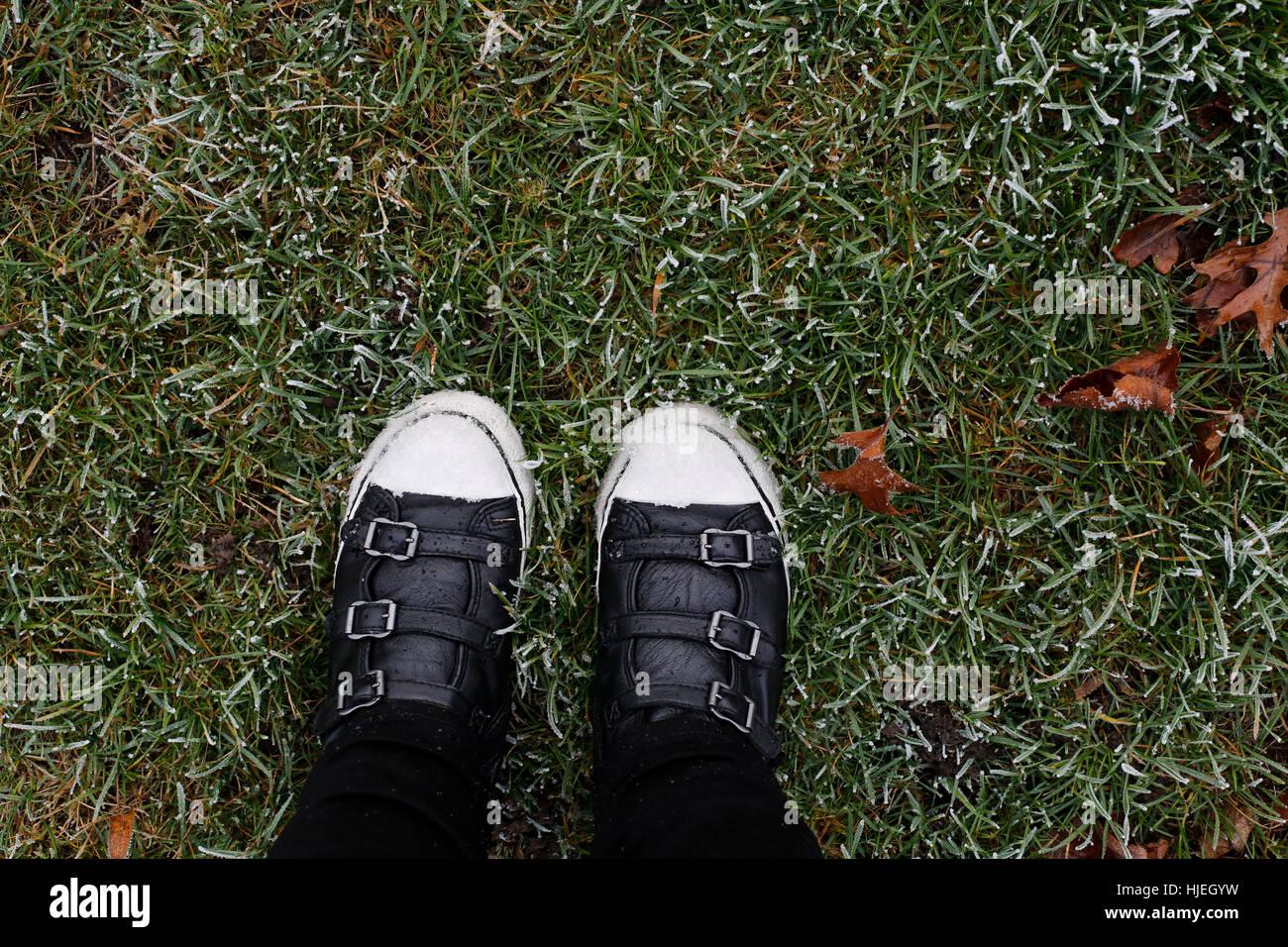 Blick von oben auf Frau Füße in schwarzen Stiefeln stehen auf dem ...