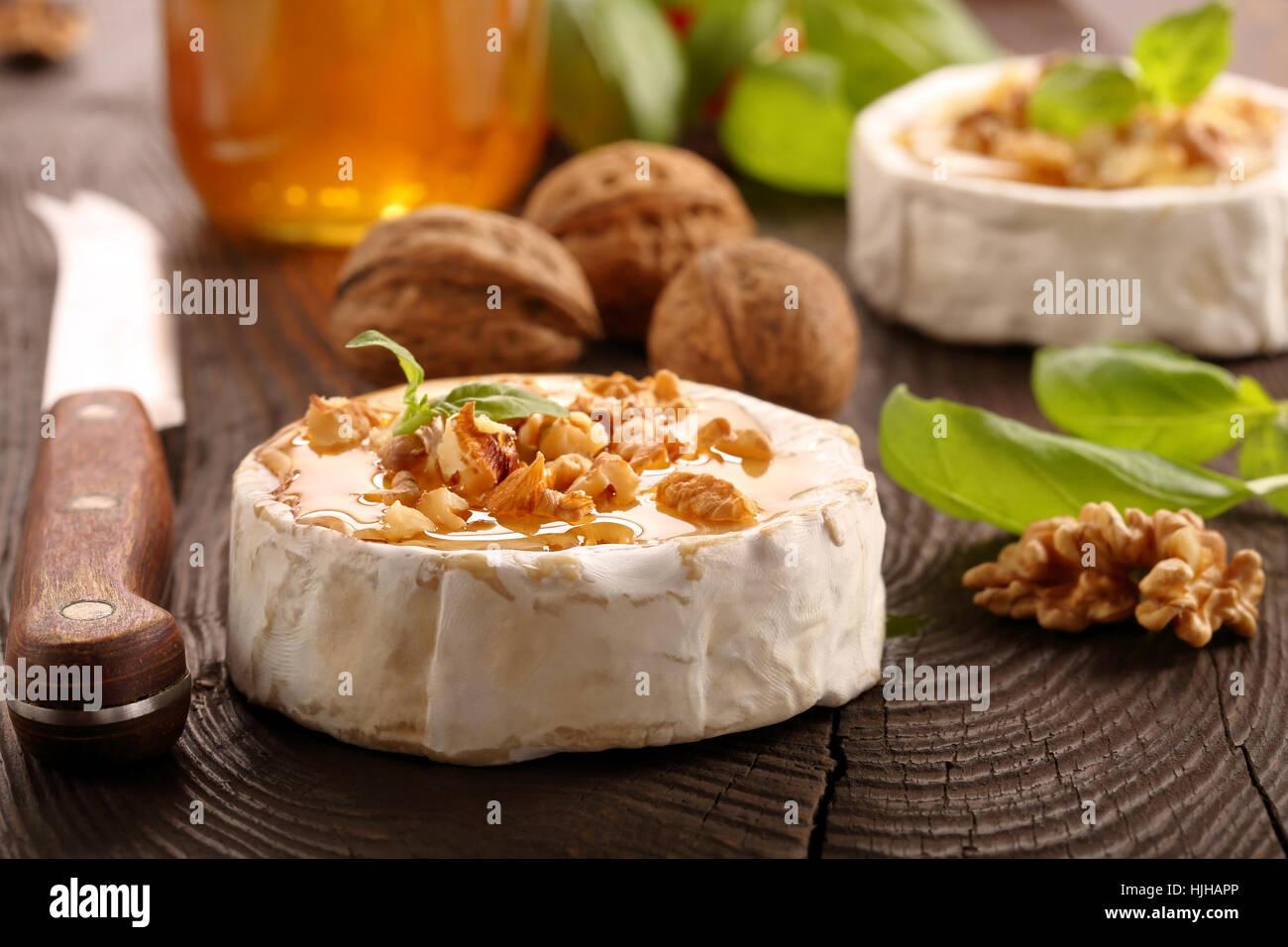 Brie Käse mit Honig und Nüssen auf alten hölzernen Hintergrund Stockbild