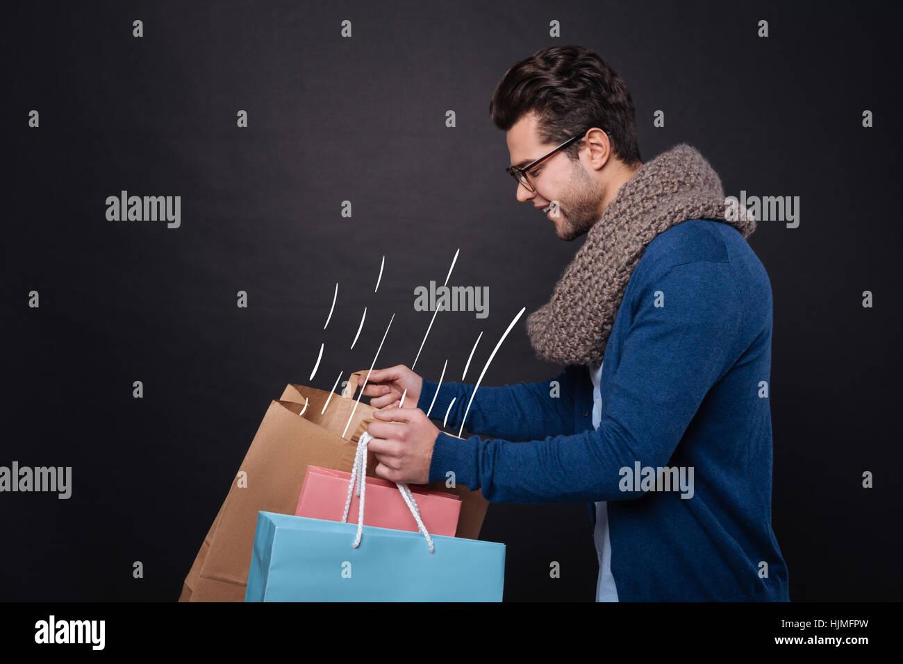 Fröhliche gut aussehender Mann sucht in seinen Taschen. Stockbild