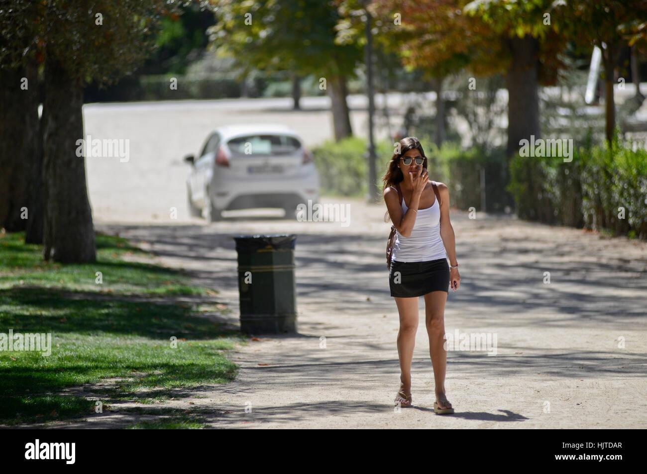Brünette Frau in Minirock auf der Straße, mit einem Auto auf dem Hintergrund Stockbild