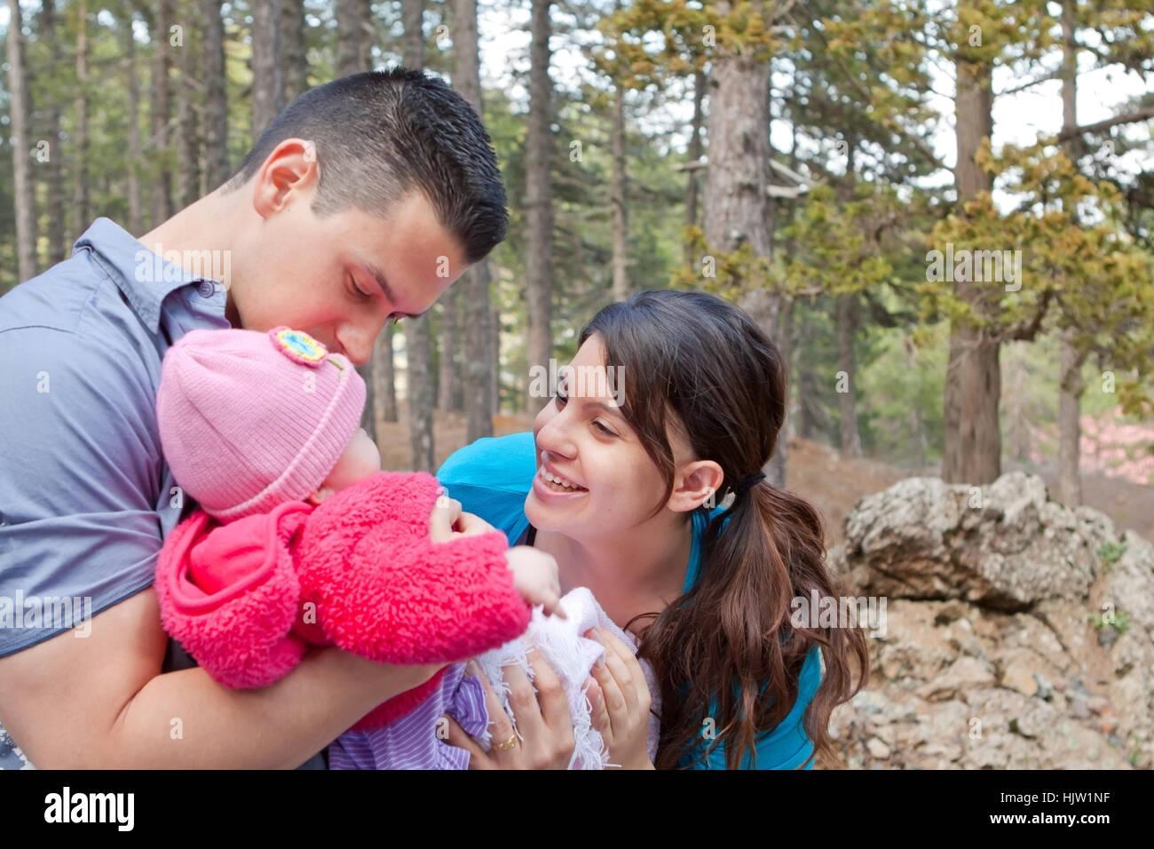 Eltern spielen mit und küssen Babymädchen Stockfoto